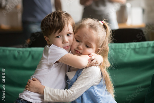 Photo Little brother hugging upset sister sitting together on couch at home, sincere t