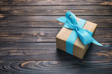 Paper Gift Box With Blue Ribbon On Dark Wood Background. Top View Vintage, Toned With Copy Space