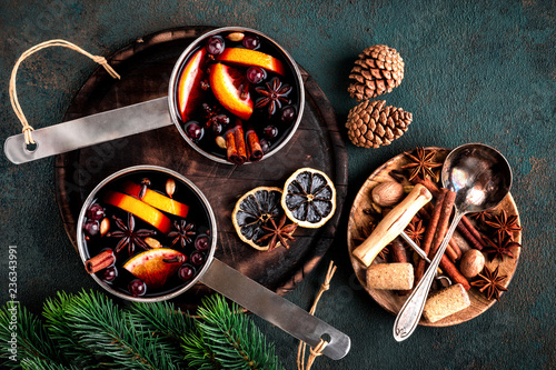 hot mulled wine cooked in two saucepan with spices, orange and cranberries on the table with Christmas fir twigs on a dark background