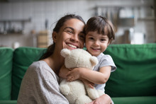 Smiling Single Young Mum Embracing Little Preschool Daughter With Toy, Playing In Living Room At Home, Mother Laughing With Child, Headshot Portrait, Cute Girl Look At Camera