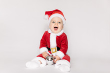 Child Happy Girl In Santa Hat On White Background With Christmas Ball. Kid Having Fun At Christmas Time. Merry Xmas Concept