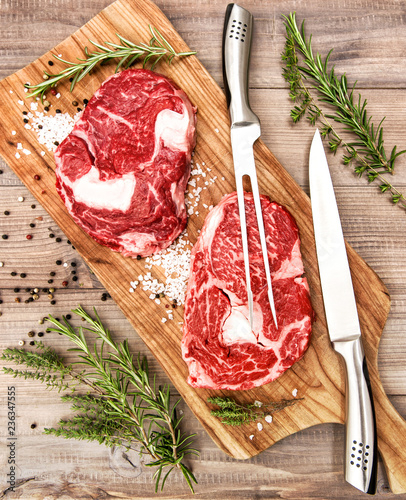 Foto op Aluminium Vlees Raw beef meat Ribeye Steak herbs spices wooden desk
