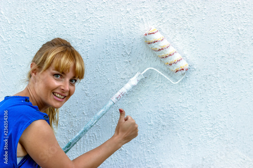 Fotografía  Happy Girl painting the wall of the room