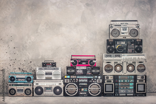 Photo Retro old school design ghetto blaster boombox stereo radio cassette tape recorders tower from circa 1980s front aged concrete wall background