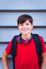 Portrait Of Smiling Schoolboy With Headphones Standing Against Wall