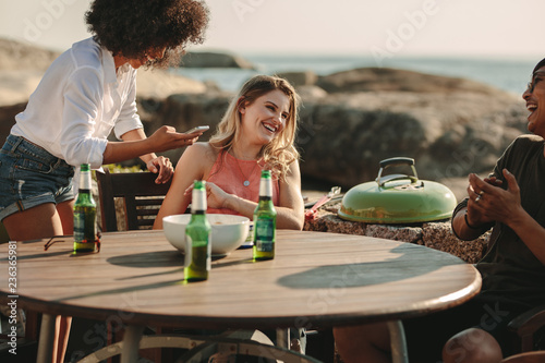 Fotomural Group of friends on a vacation enjoying at a beachside table