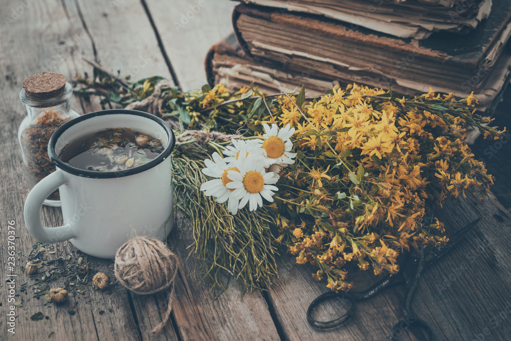 Fototapety, obrazy: Enameled mug of healthy tea, bunches of medicinal herbs and stack of old books. Herbal medicine.