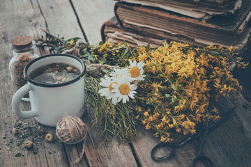 Enameled mug of healthy tea, bunches of medicinal herbs and stack of old books. Herbal medicine.