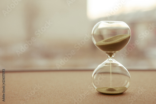 Sand running through the bulbs of an hourglass measuring the passing time in a countdown to a deadline, on a blur background