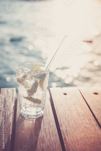 Cocktail at the wooden pier during sunset. Luxury vacation resort. Holiday getaway concept