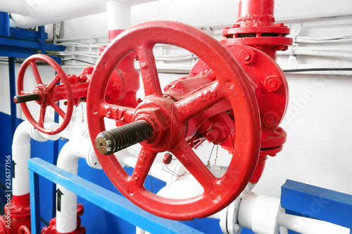 Photo  red valve of system of water supply at the industry.