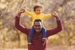 Smiling father holding his son on shoulder and looking at camera. Portrait of happy african dad little boy smiling in the garden.