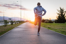 Fitness Woman Runner Stretching Legs Before Run On The Road.