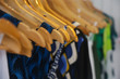 Variety of colorful summer clothes hanging on the wooden hangers, close up