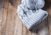 Wool Grey Hat, Knitting Needles And Yarn On Wooden Background.