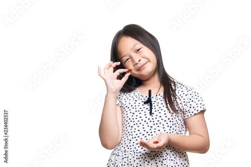 Obraz na plátne Cute kid southeast asian girl age 7 years take pill or vitamin lecithin