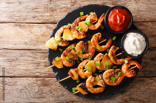Fresh kebabs made from shrimps and pineapple slices decorated with green onions served with sauces close-up on a slate plate. Horizontal top view