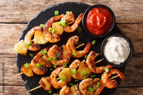 Grilled kebabs with shrimp with fresh pineapples and green onions served with sauces close-up on a slate plate. Horizontal top view
