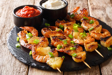 Delicious Appetizer Of Kebab Grilled Shrimp And Pineapple Slices Served With Sauces Close-up. Horizontal