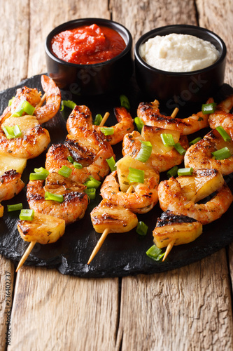 Shrimp kebabs with pineapples and green onions filed with sauces close-up on a slate plate on a table. vertical
