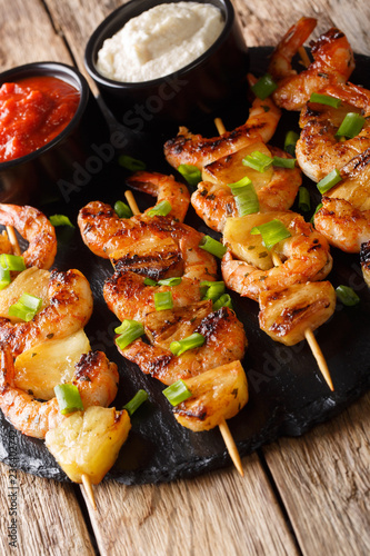 Delicious shrimp kebab with pineapples served with two sauces close-up on a table. vertical