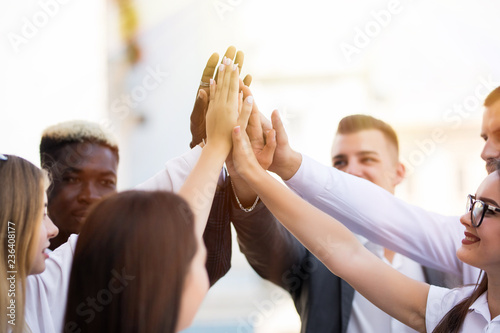 Happy successful multiracial business team giving a high fives gesture as they l Canvas Print