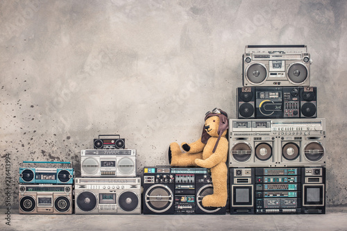 Teddy Bear toy with leather aviator's hat and goggles sitting on retro old school design ghetto blaster boombox stereo radio cassette tape recorders tower from circa 80s Canvas Print