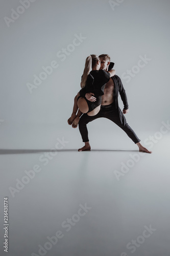 Two young modern ballet dancers in studio