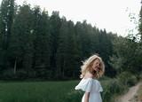 Fototapeta Las - Young pretty girl in a green field