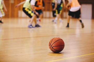 Pozadina igre treninga košarke. Košarka na drvenom podu zatvori izbliza sa zamućenim igračima koji igraju košarku u pozadini