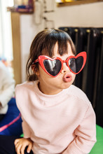 Dark-haired Little Girl Wearing Bright Red Heart Shape Sunglasses