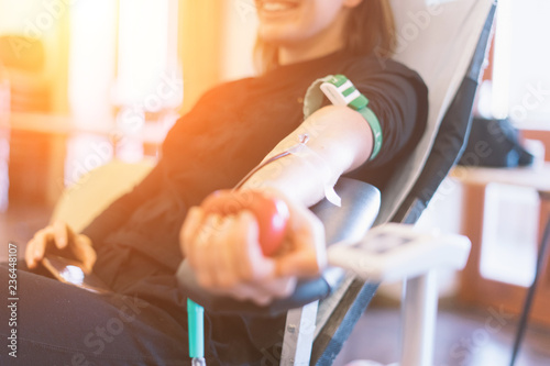 Fotomural  young woman as blood donor at donation with a bouncy ball holding in hand