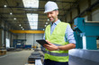 Smiling man wearing shirt and safety vest using tablet in factory