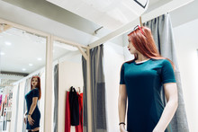 Young Beautiful Girl Trying On New Green Dress In The Fitting Room In Boutique.