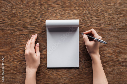 Obraz cropped view of person holding pen over blank notebook on wooden background - fototapety do salonu