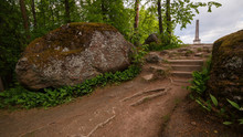 The Path Leads Out Of The Forest To An Open Area With An Obelisk. Large Stones Around The Stairs.