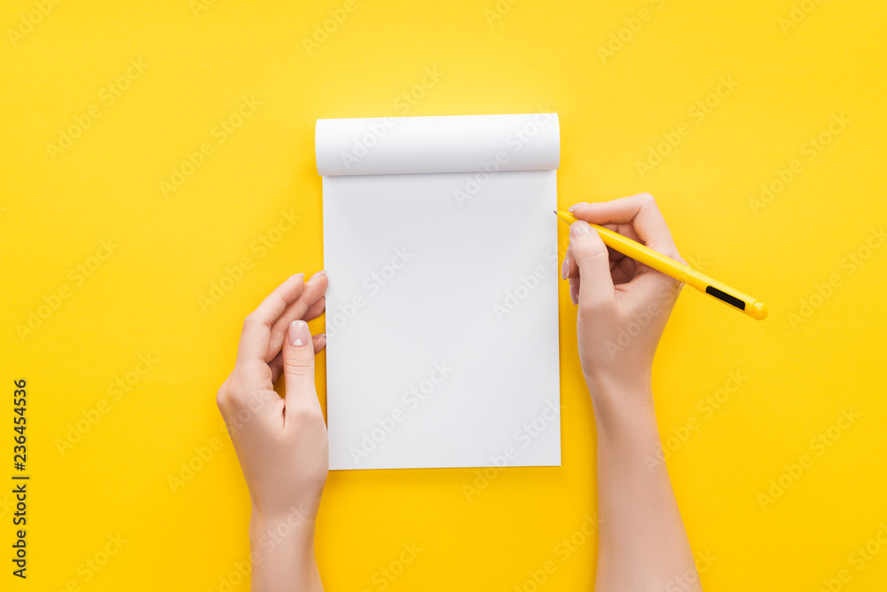 Fototapeta  partial view person holding pen over blank notebook on yellow background