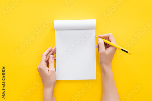 partial view person holding pen over blank notebook on yellow background Wallpaper Mural