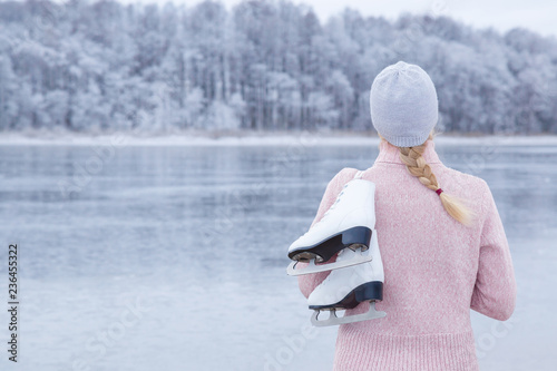 Cuadros en Lienzo Young blond woman in pink sweater and hat staring at ice of lake and holding white skates over shoulder in freezing winter day