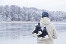 Young Man In White Knitted Jacket And Hat Staring At Ice Of Lake And Holding Black Skates Over Shoulder In Freezing Winter Day. Back View Of Ice Skater. Outdoor Activities On Weekends In Cold Weather.