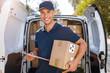 Leinwandbild Motiv Delivery man standing in front of his van