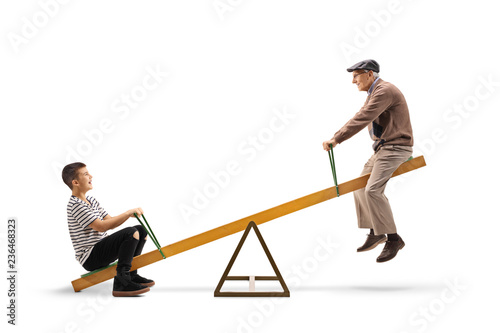 Fotografie, Obraz  Young boy and an elderly man riding on a seesaw