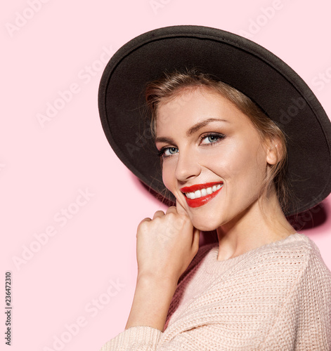 Close-up portrait of young woman wearing elegant hat and feeling cheerful. Attractive blonde model with bright red lips on pink background. Modern fashion concept Wall mural