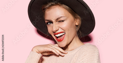 Obraz Close-up fashion portrait of gorgeous lady expressing happiness. Stylish female with beautiful smile and perfect makeup posing in studio on pink background - fototapety do salonu