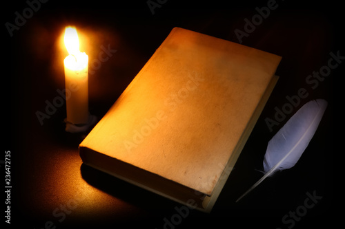 old book, burning candle and feather in the dark Tablou Canvas