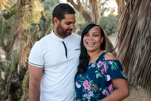 Portrait Of Happy Wife Standing With Husband Against Trees In Park
