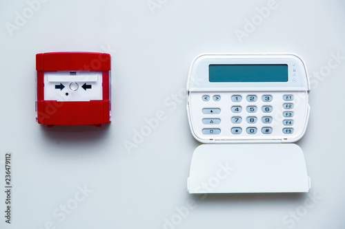Photo Fire safety button in a red box on a gray wall near a white alarm control panel with security password input buttons, front view on a bright wall indoors