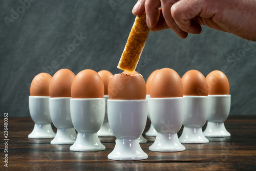 Hand Dipping Toast Soldier Into Boiled Eggs in Egg Cups on a Table