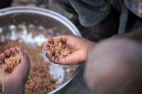 Fotografía kids eating brown rice and fish in Africa - closeup