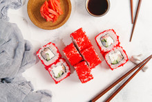 Overhead View Of Red Sushi Rolls With Chopsticks And Salmons By Dip Served On Table